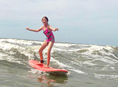 A young lady learns to surf with the help of Charleston Surf Lessons on Folly Beach.