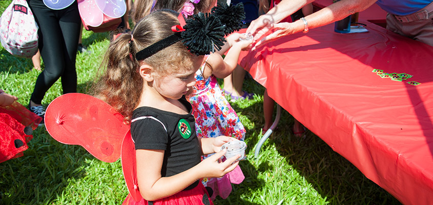 Volunteers distribute ladybugs to children to release into the gardens. © 2016 Audra L. Gibson