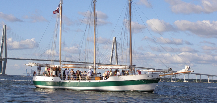 Guests enjoy a sail in Charleston Harbor with the Ravenel Bridge in the background.